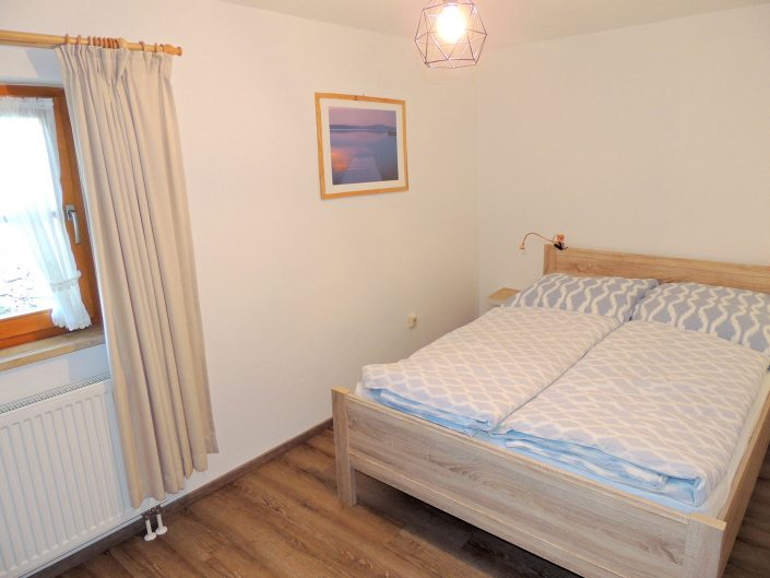 Das Schlafzimmer der Ferienwohnung Berghäusl in Oberau bei Berchtesgaden verfügt über ein bequemes Doppelbett sowie über einen 3-türigen Schrank. Familie Brandner freut sich auf Sie.